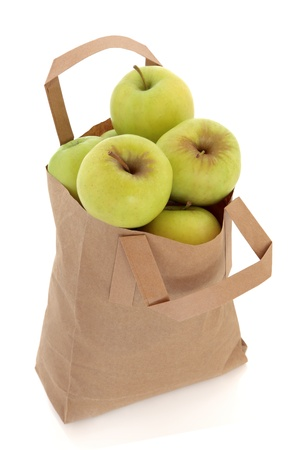 Golden delicious apple fruit in a brown paper recycled carrier bag isolated over white background  photo
