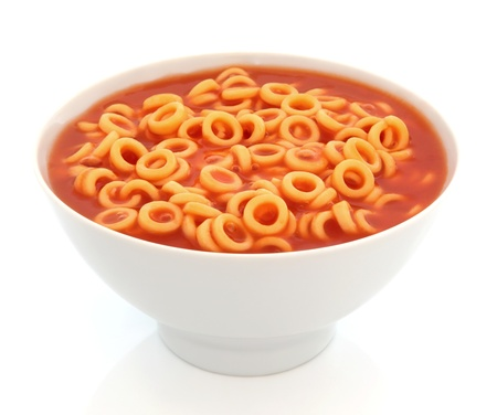 Spaghetti pasta hoops in tomato sauce in a porcelain bowl with fork over white background  Stock Photo - 13174839