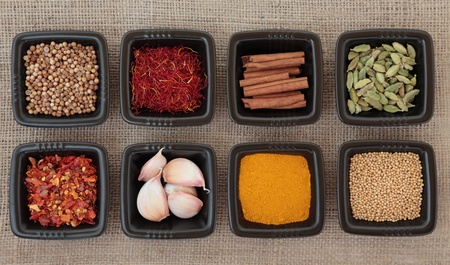Spice collection of coriander and mustard seed, chili flakes, saffron,  cinnamon sticks, cardamom pods, turmeric, garlic cloves in black dishes on hessian sacking background  photo