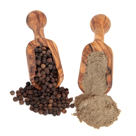 Black peppercorn spice and pepper powder in olive wood scoops over white background