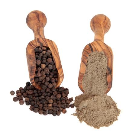 pepe nero: Spezie pepe nero e pepe in polvere in legno di ulivo scoop su sfondo bianco