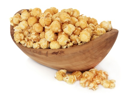 bowls of popcorn: Butterscotch popcorn in an olive wood bowl and loose over white background  Stock Photo