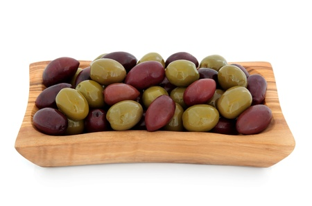 antipasti: Green and black olives in an olive wood bowl over white background