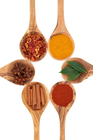pepper flakes: Turmeric, bay leaf herb, chili flakes, star anise, cinnamon sticks and cayenne pepper spices in olive wood spoons over white background