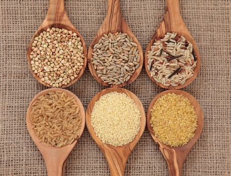 Cereal and grain selection of bulgur wheat, buckwheat, couscous, rye grain and brown and wild rice in olive wood spoons on hessian sacking background Stock Photo - 13373296