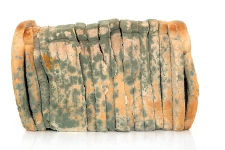흰색 배경 위에 곰팡이가 핀 얇게 썬 빵 덩어리