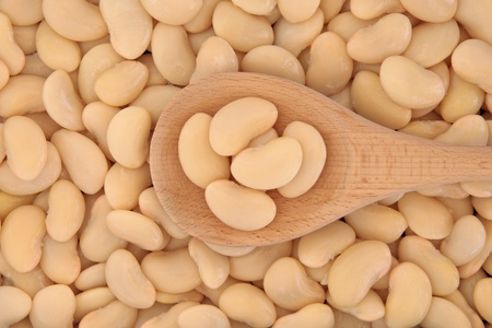 lima: Butter beans in a wooden cooking spoon and forming a textured background  Stock Photo
