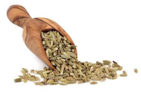 Fennel seed in an olive wood scoop over white background
