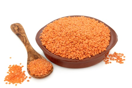 pulses: Red lentil pulses in a terracotta bowl,, olive wood spoon and loose over white background