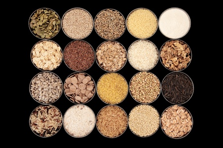 bulgur: Large selection of cereal, seed and grain food in bowls over black background  Stock Photo