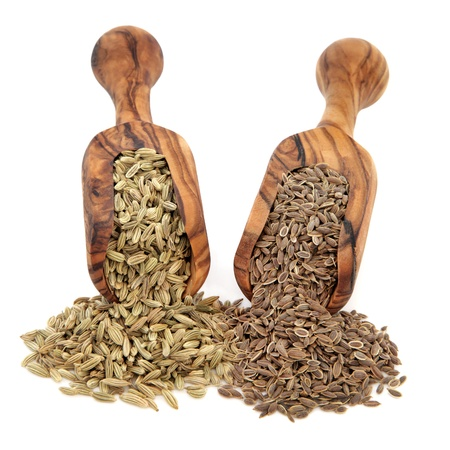 Fennel and dill seed in an olive wood scoop over white background  photo