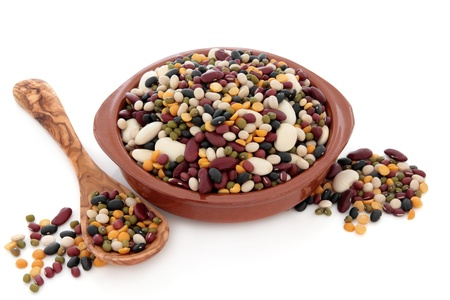 pulses: Dried mixed pulses for soup mixture in a terracotta bowl, olive wood spoon and loose over white background  Stock Photo