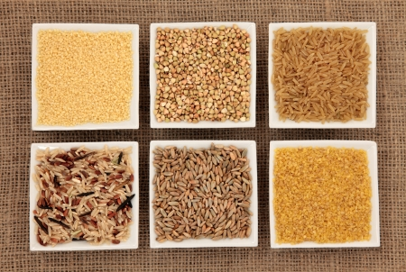 bulgur: Cereal and grain selection of bulgur wheat, buckwheat, couscous, rye grain and brown and wild rice in white porcelain dishes on hessian sacking background