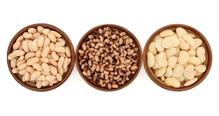 baked beans: Cooked bean and pea varieties of cannelini, black eyed peas and butter beans in terracotta bowls over white background  Stock Photo