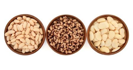 Haricots cuits et les variétés de pois de cannelini, black eyed peas et haricots beurre en terre cuite bols sur fond blanc