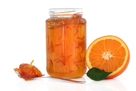 marmalade: Marmalade in a jar with half an orange, leaf and jam in a spoon over white background