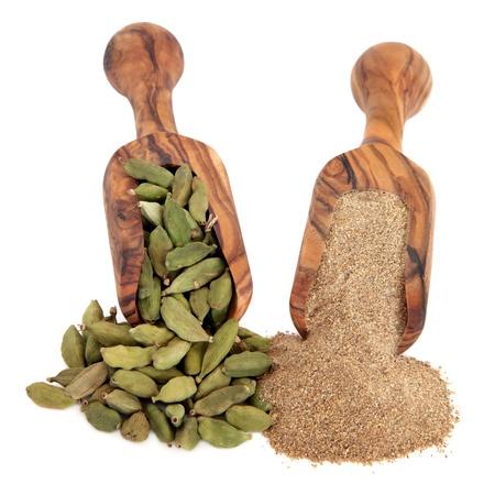 Bacche di cardamomo e polvere di spezie a terra in legno d'ulivo scoop su sfondo bianco