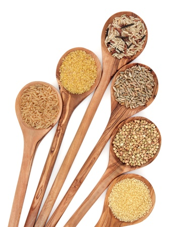 Healthy food of brown and wild rice, bulgur wheat, couscous, rye grain and  buckwheat grain in olive wood spoons over white background  photo