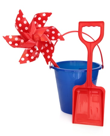 beach toys: Blue plastic beach toy bucket, red spade and polka dot windmill over white background