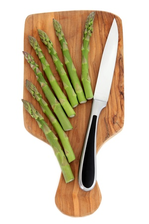 Asparagus spears on an olive wood chopping board with stainless steel kitchen knife over white background Stock Photo - 14124330