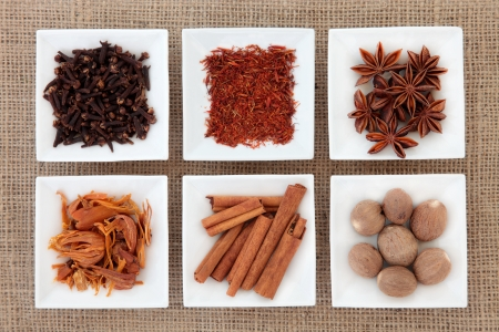 mace: Saffron, star anise, cloves, cinnamon sticks, nutmeg and mace spice in white porcelain dishes over hessian background