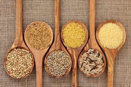 Cereal and grain selection of bulgur wheat, buckwheat, couscous, rye grain and brown and wild rice in olive wood spoons on hessian sacking background  Stock Photo - 14254841