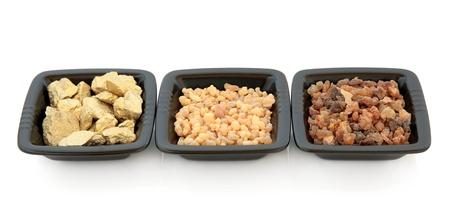 incienso: Oro, incienso y mirra en los platos cuadrados negros sobre fondo blanco