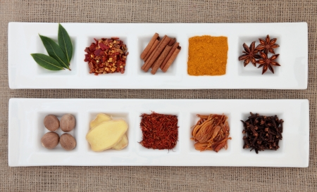 sampler: Spice collection of chili flakes, cinnamon, turmeric, star anise, nutmeg, ginger, saffron, mace, cloves and bay leaf herb in white porcelain dishes over hessian background  Stock Photo