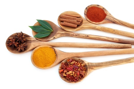 pepper flakes: Turmeric, bay leaf herb, chili flakes, star anise, cinnamon sticks and cayenne pepper spice in olive wood spoons over white background
