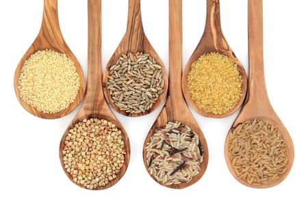 bulgur: Cereal and grain selection of bulgur wheat, buckwheat, couscous, rye grain and brown and wild rice in olive wood spoons on white background