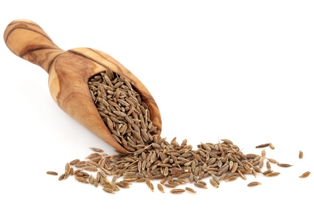 Cumino in uno scoop legno di ulivo e sparsi su sfondo bianco