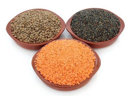 Red, green and black lentil selection in three terracotta bowls over white background