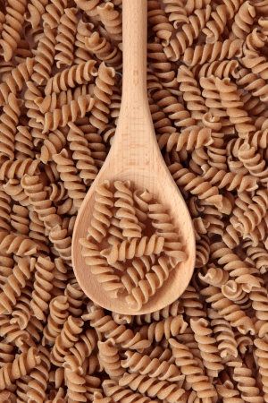 Fusilli pasta on a wooden spoon and forming a background  Stock Photo - 14607229