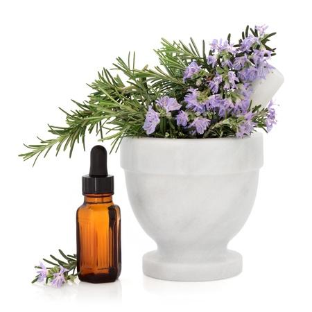 mortero: Romero de hierbas en un mortero de mármol con la maja con la botella de aceite esencial de aromaterapia sobre fondo blanco Foto de archivo