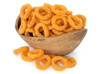 unhealthy snack: Onion ring crisps in an olive wood bowl and loose over white background  Stock Photo