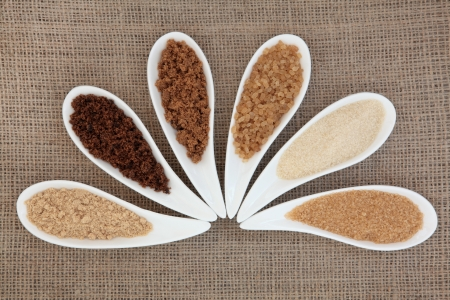 Selection of demarara, granulated, molasses, muscovado, crystal and light brown sugar in white bowls over hessian background  photo