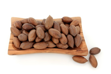 whole pecans: Pecan nuts in an olive wood bowl and loose over white background