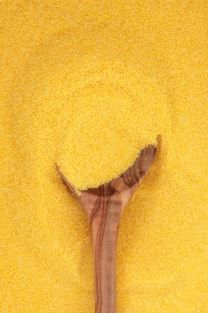 polenta: Polenta in an olive wood spoon and forming a background