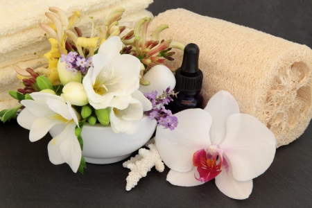 Freesia, orchid, honeysuckle and lavender flowers, aromatherapy spa bottle, towels and exfoliating scrub with coral shell over slate background  photo