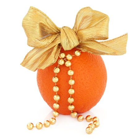 Orange fruit decoration with bow and  gold bead chain over white background  photo