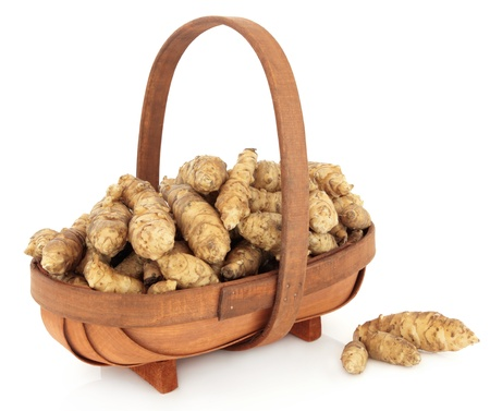 Jerusalem artichoke raw vegetables in a rustic wooden basket and loose over white background