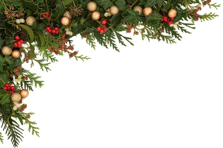 Christmas seasonal  border of holly, ivy, mistletoe, cedar leaf sprigs with pine cones and gold baubles over white background