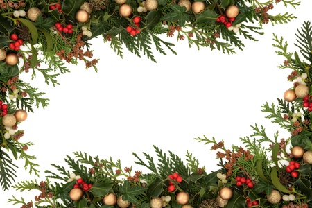 Christmas seasonal  border of holly, ivy, mistletoe, cedar leaf sprigs with pine cones and gold baubles over white background  photo