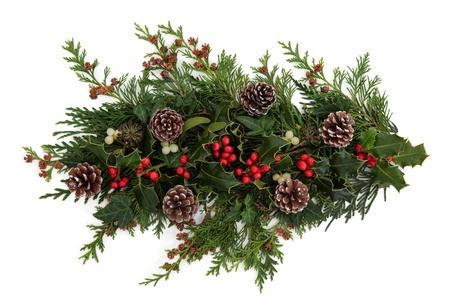 Winter and christmas decorative floral arrangement of holly with red berry clusters, mistletoe, ivy and cedar leaf sprigs with pine cones over white background  photo