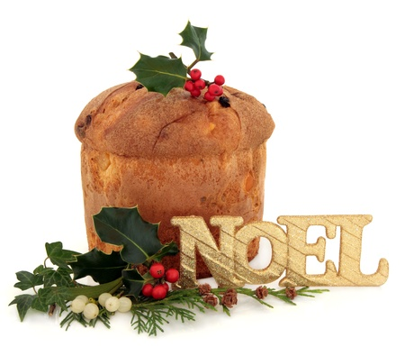 fruitcake: Panetone christmas cake with noel glitter sign, holly, mistletoe, ivy and cedar cypress leaf sprig decoration over white background   Stock Photo