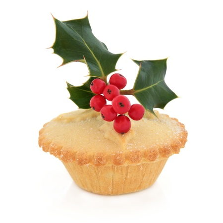 Christmas mince pie with holly and red berry leaf sprig over white background