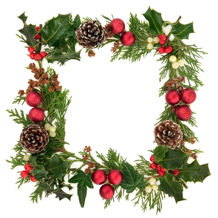 Christmas decorative border of holly, ivy, mistletoe, cedar leaf sprigs with pine cones and red baubles over white background