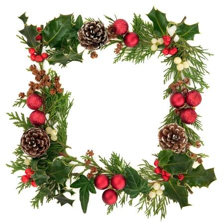 houx: Noël bordure décorative de houx, de lierre, le gui, les brins de feuilles de cèdre avec des pommes de pin et des boules rouges sur fond blanc Banque d'images