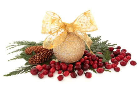 Christmas glitter bauble with bow and cranberry fruit with ivy, cedar cypress leaf sprigs and pine cones over white background  photo