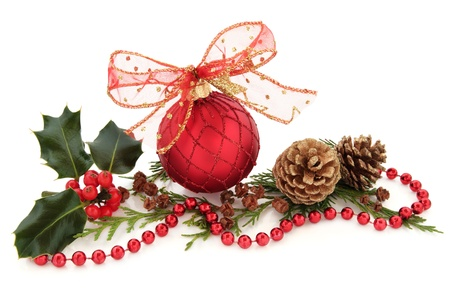 Christmas red sparkling bauble with glitter bow surrounded by holly and cedar leaf sprigs with gold pine cones over white background Stock Photo - 15476574